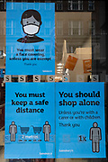 Outside a a local Sainsburys supermarket in Mayfair, posters urger shoppers to observe social distancing, to shop alone and wear a face covering, on 4th March 2021, in London, England.