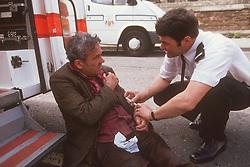 Ambulance man assisting elderly patient,