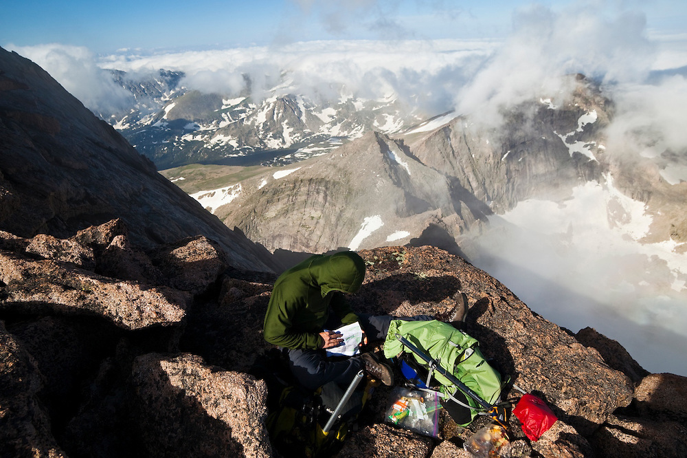 James Meldrum studies a topo map on the summit of Longs Peak, Rocky Mountain National Park, Colorado. Chiefs Head is visible in the background.