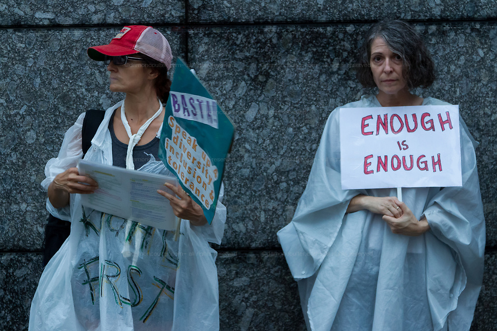 """Organisers:, Sarajean Rossitto (left) and Jenise Treuting (right) join other  American and Japanese  people at the  """"Enough is Enough"""" rally in Toranomon, Tokyo Japan, Tuesday August 15th 2017. Around 20 people gathered to take part in a global day of action demanding fairer policies in the United States that do not favour only the rich and do not remove human rights from ordinary people. A silent vigil was held for 30 minutes at 6pm so that the voices that could be heard after spoke louder. This is the closest it is possible to protest to the US embassy in Tokyo."""