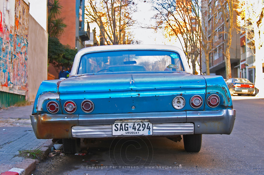 A classic but run down blue and white old American car parked in a street in the city Montevideo, Uruguay, South America