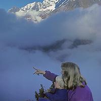 NEPAL, HIMALAYA. Meredith & Benjamin Wiltsie admire view above Namche Bazar. Mount Thamserku bkg. (MR)