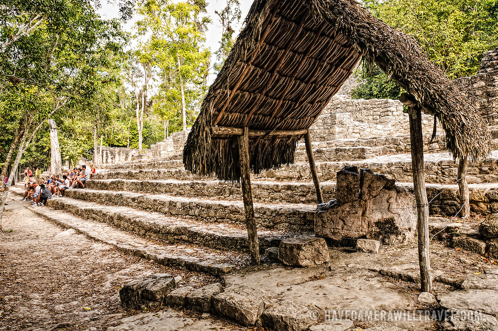 In the foreground, a thatched roof protects a stone with inscriptions. In the background, a group of students sit on the lower steps of La Iglesia at Coba, an expansive Mayan site on Mexico's Yucatan Peninsula not far from the more famous Tulum ruins. Nestled between two lakes, Coba is estimated to have been home to at least 50,000 residents at its pre-Colombian peak.