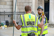 """""""Please keep your distance 2 meters,"""" says in the back of a worker from """"Ideal Installations"""" working in London's Whitehall Building on Wednesday, May 27, 2020. The prime minister's populist appeal has been hammered by the news that, as the coronavirus outbreak raged, chief adviser Cummings drove 250 miles (400 kilometres) to his parents' house while he was falling ill with suspected COVID-19 allegedly flouting lockdown rules that the government had imposed on the rest of the country. (Photo/ Vudi Xhymshiti)"""
