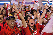 03 JULY 2011 - BANGKOK, THAILAND:   A woman in Bangkok reacts to news that the Pheu Thai party and Yingluck Shinawatra won the Thai elections Sunday night. Yingluck Shinawatra and the Pheu Thai Party scored a massive landslide win in the Thai election Sunday. Pheu That is estimated to have won more than 300 seats in Thailand 500 seat parliament, so they won an absolute majority and could govern without having to form a coalition with minor parties. Pheu Thai is the latest incarnation of deposed former Prime Minister Thaksin Shinawatra's political party. Yingluck is his youngest sister. Many observers expect legal challenges to the Pheu Thai victory and the election does not completely resolve Thailand's difficult political history of the last five years.    PHOTO BY JACK KURTZ