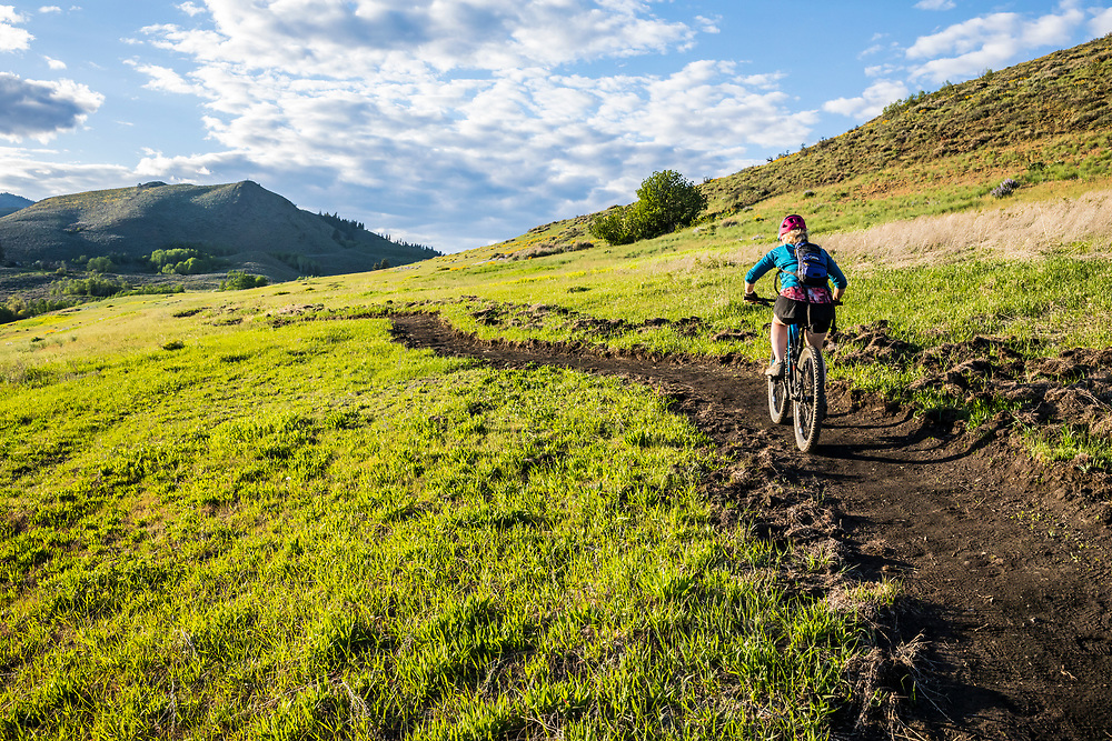 A woman climbing the trail on Lewis Butte outside Winthrop, Washington on a sunny afternoon in May.