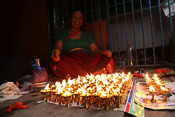 August 7, 2017 - Lalitpur, Nepal - A Hindu woman lit butter lamps offering prayers to Lord Shiva during Monday of Shrawan month(Shrawan Somvar) at Kumbheshwor temple in Lalitpur. Shrawan month is considered as the holiest month of the year and each Somvar (Monday) of this month is known as Shrawan Somvar, Hindu married women pray the long and prosperous life for their husbands and unmarried wish for a good husband. (Credit Image: © Archana Shrestha/Pacific Press via ZUMA Wire)