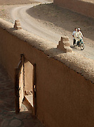 A motorcycle drives down a street in the village of Dadès in the Skoura Oasis in Morocco
