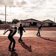 Guyanese workers playing football with their bosses (Brazilians) in front of the factory in Lethem, Guayana, border Brazil - Guyana