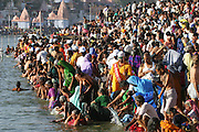 Pilgrims bathing in the Shipra River at the Kumbh Mela festival, Ujjain, Madhya Pradesh, India. The Kumbh Mela festival is a sacred Hindu pilgrimage held 4 times every 12 years, cycling between the cities of Allahabad, Nasik, Ujjain and Hardiwar.  Participants of the Mela gather to cleanse themselves spiritually by bathing in the waters of India's sacred rivers.  Kumbh Mela is one of the largest religious festivals on earth, attracting millions from all over India and the world.  Past Melas have attracted up to 70 million visitors.