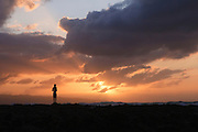 A lone man looks out over the Paciifc Ocean at sunset on the Norht Shore of Oahu, Hawaii.