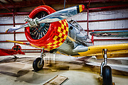 """Designated the BT-13 by the Army Air Corps and the SNV-2 by the Navy, the Vultee Valiant was the next aircraft cadet pilots flew after learning to fly the PT-17 (Stearman), PT-19 or PT-22. Less forgiving than these primary trainers, the SNV/BT-13 required the student pilot to pay more attention to the aircraft in flight. Additionally in the SNV/BT-13, student pilots were introduced to advanced items such as a two-way radio for communication with the ground.<br /> <br /> Designed in the late 1930s, the SNV/BT-13 was chosen in 1939 by the U.S.A.A.C. and by the Navy in 1940 for use as a basic trainer. A confidence builder for green pilots, the SNV/BT-13 has been described as a """"roomy, noisy, aerobatic and smelly"""" airplane and received the ignominious nickname """"The Vultee Vibrator"""" from its pilots. The aircraft sharpened the pilot's skills and introduced students to the feel of a more complex and powerful aircraft. Unlike the primary trainers that were fitted with a fixed pitch prop, the SNV/BT-13 was equipped with a two position, variable-pitch propeller requiring greater skill to fly. After mastering the SNV/BT-13, pilots advanced to the AT-6 Texan for fighter pilot training or a twin-engined advance trainer for bomber or transport pilot training.<br /> <br /> Once America was fully involved in World War II, Vultee received orders for more than 10,000 SNV/BT-13s, making the plane one of the most important American trainer aircraft of the war. Due to a shortage of the BT-13's Wasp Junior radial engine, Vultee began to fit the Wright R-975-11 radial to BT-13 airframes. A total of 1,693 BT-15s, as these planes were called, were built before the end of the war. Today, the few airworthy SNV/BT-13s or BT 15s left are very popular with warbird collectors and can often be seen at airshows around the country.<br /> <br /> The paint scheme of the SNV-2 on display is authentic for a SNV-2 based at the Naval Air Station in Corpus Christi, Texas during World War II. This SNV-2 was"""