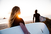 Surfers standing in the golden sunlight looking out to sea at La Rocco Tower, St Ouen's Bay, Jersey, CI