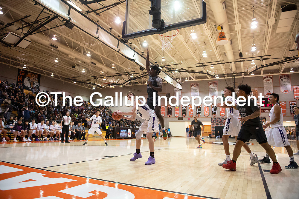 Miyamura's Chris Mortensen (32) looks to the basket as Spring Valley's James Webster (23) defends at the Gallup Invitational boys basketball tournament Thursday, Jan 2 at Gallup High School.