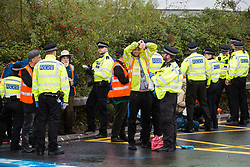 Metropolitan Police officers arrest Insulate Britain climate activists who had blocked a M25 slip road at Junction 14 close to Heathrow airport as part of a campaign intended to push the UK government to make significant legislative change to start lowering emissions on 27th September 2021 in Colnbrook, United Kingdom. The activists are demanding that the government immediately promises both to fully fund and ensure the insulation of all social housing in Britain by 2025 and to produce within four months a legally binding national plan to fully fund and ensure the full low-energy and low-carbon whole-house retrofit, with no externalised costs, of all homes in Britain by 2030.