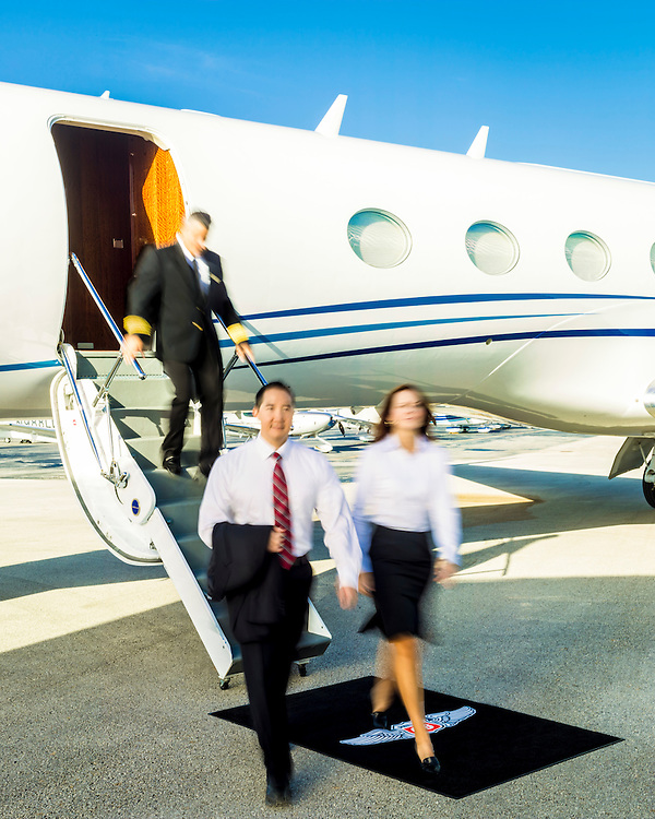 Executives exit a Gulfstream business jet at Opa-locka Executive Airport, near Miami.  Commissioned as advertising for Phillips 66 Aviation Fuels.<br />