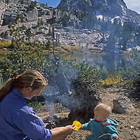 A mother players with her toddler son during a picnic by Emerald Lake in John Muir Wilderness, Sierra Nevada, California.