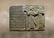 """Photo of Hittite monumental relief sculpted orthostat stone panel of Royal Buttress. Basalt, Karkamıs, (Kargamıs), Carchemish (Karkemish), 900-700 B.C. Anatolian Civilisations Museum, Ankara, Turkey.<br /> <br /> Hieroglyph panel (left) - Discourse of Yariris. Yariris presents his predecessor, the eldest son Kamanis, to his people. <br /> Right Panel - King Araras holds his son Kamanis from the wrist. King carries a sceptre in his hand and a sword at his waist while the prince leans on a stick and carries a sword on his shoulder. <br /> <br /> Hieroglyphs reads; """"This is Kamanis and his siblings.) held his hand and despite the fact that he is a child, I located him on the temple. This is Yariris' image"""".  <br /> <br /> Against a brown art background. .<br />  <br /> If you prefer to buy from our ALAMY STOCK LIBRARY page at https://www.alamy.com/portfolio/paul-williams-funkystock/hittite-art-antiquities.html  - Type  Karkamıs in LOWER SEARCH WITHIN GALLERY box. Refine search by adding background colour, place, museum etc.<br /> <br /> Visit our HITTITE PHOTO COLLECTIONS for more photos to download or buy as wall art prints https://funkystock.photoshelter.com/gallery-collection/The-Hittites-Art-Artefacts-Antiquities-Historic-Sites-Pictures-Images-of/C0000NUBSMhSc3Oo"""