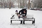 A Polish man leans over to put the finishing touches to two small snowmen that now occupy a park bench on Goose Green in East Dulwich, Southwark, South London, England. This otherwise green space has seen snow falls that have gripped this part of the capital with unsalted road surfaces and commuting nightmares. But this young man is having fun with his diminutive snowy creations who have been dressed up in his and a friend's glasses, their scarves and gloves and with locally-found twigs. The park is relatively quiet with only a hint of the chaos elsewhere but the time spent on pointless pursuits is one way of enjoying adverse weather, rather than the more serious business of getting to work, proving also that snow brings out the childish nature in us all.