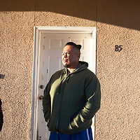 Jason Joe, center, and Phoebe Morgan stand in front of Joe's home in the Tse'ii'ahi' Navajo Housing Authority Subdivision in Standing Rock, New Mexico Thursday. Since moving into the home Joe has had many roof issues including missing shingles and water leaks.