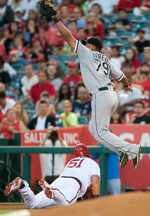 The Angels' Ji-Man Choi dives back to first as the White Sox' Jose Abreu leaps for the ball, landing on Choi's hand in the third inning at Angel Stadium on Friday.<br /> <br /> ///ADDITIONAL INFO:   <br /> <br /> angels.0716.kjs  ---  Photo by KEVIN SULLIVAN / Orange County Register  -- 7/15/16<br /> <br /> The Los Angeles Angels take on the Chicago White Sox at Angel Stadium.