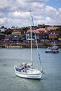 A woman sails a white yacht names Crusoe 2 out of Folkestone Harbour while a man stands on deck looking out to sea, Folkestone, Kent, England, United Kingdom.