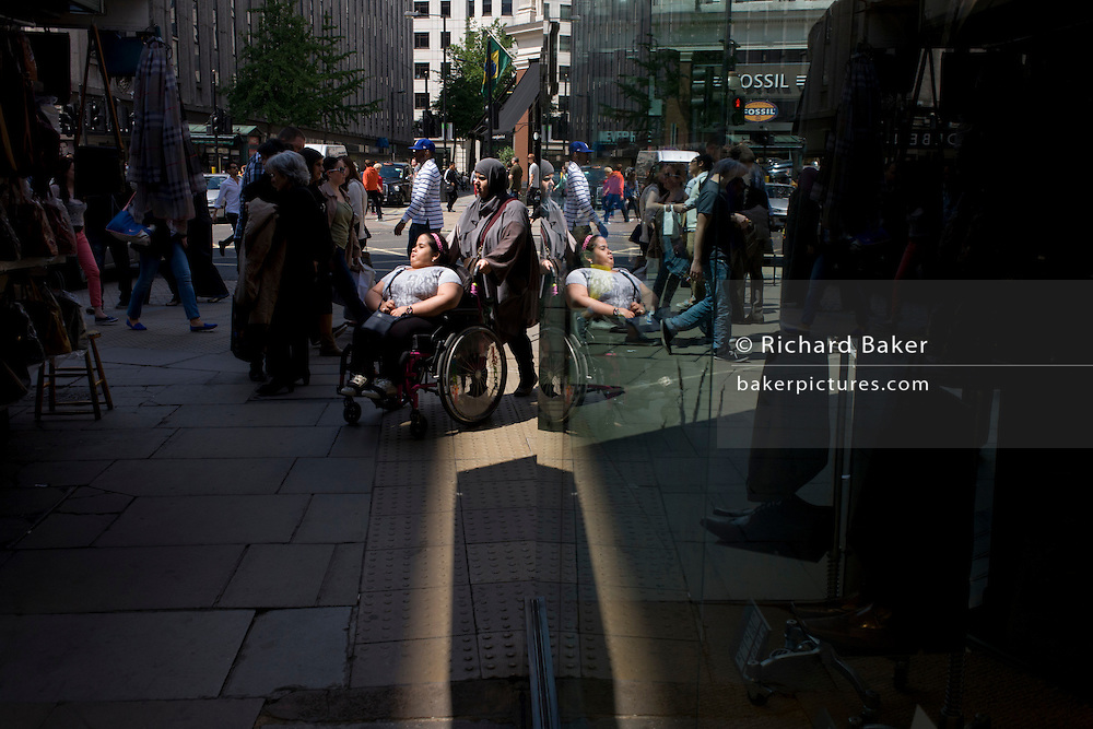 A Muslim woman pushes a young girl confined to a wheelchair in a central London street.