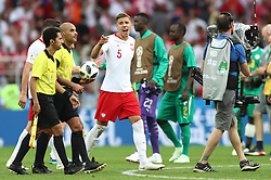 Poland's Jan Bednarek (centre) exchanges word with the officials after the final whistle