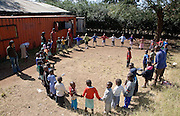 Children playing school games outdoors with teachers and volunteers standing by. The MADICAA school (makadara division campaign against aids) in Makadara, Kenya, it is a Pre-primary/nursery school that started in 2006.
