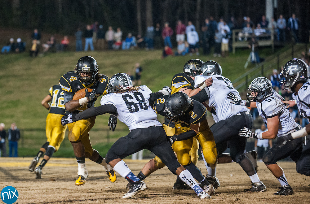Concord's Rocky Reid (4) tries to get around Forestview's Xavier Davis during the semi finals of the NCHSAA 3A playoffs Friday night at Concord High School. The Spiders defeated Forestview 35-14 to secure a spot in the state championship game.