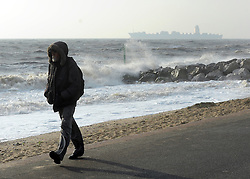 © Licensed to London News Pictures. 24/10/2011. Felixstowe, UK. A man walks along the seafront as a container ship heads out to sea from Felixstowe Harbour. Windy weather along Felixstowe promenade today 24th October 2011. Parts of the UK are braced for wet and windy weather over the next 24hrs . Photo: Stephen Simpson/LNP