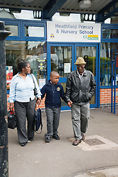 Little boy being collected by his grandparents from primary school,