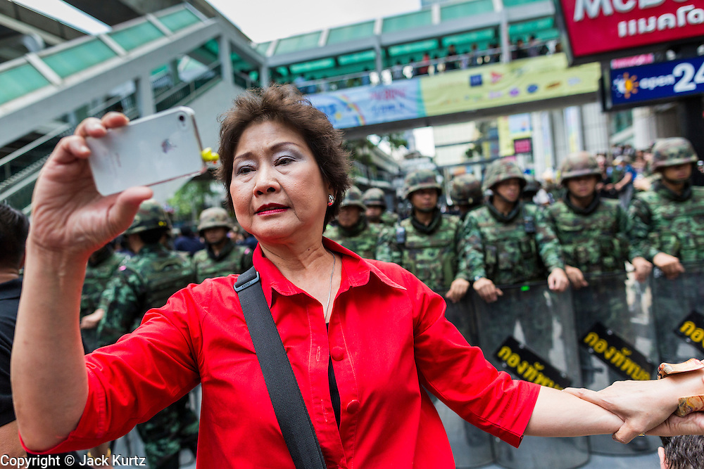 """25 MAY 2014 - BANGKOK, THAILAND: A Thai """"Red Shirt"""" supporter of the ousted civilian government takes a """"selfie"""" of herself in front of soldiers at a demonstration against the military junta. Public opposition to the military coup in Thailand grew Sunday with thousands of protestors gathering at locations throughout Bangkok to call for a return of civilian rule and end to the military junta.     PHOTO BY JACK KURTZ"""
