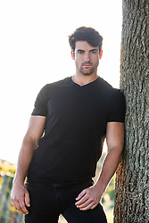 handsome man leaning against a tree