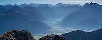 Climber on summit of Aggenstein (1987m) with Tannheimer Tal (Aus.) in background, Allgäu, Bavaria, Germany