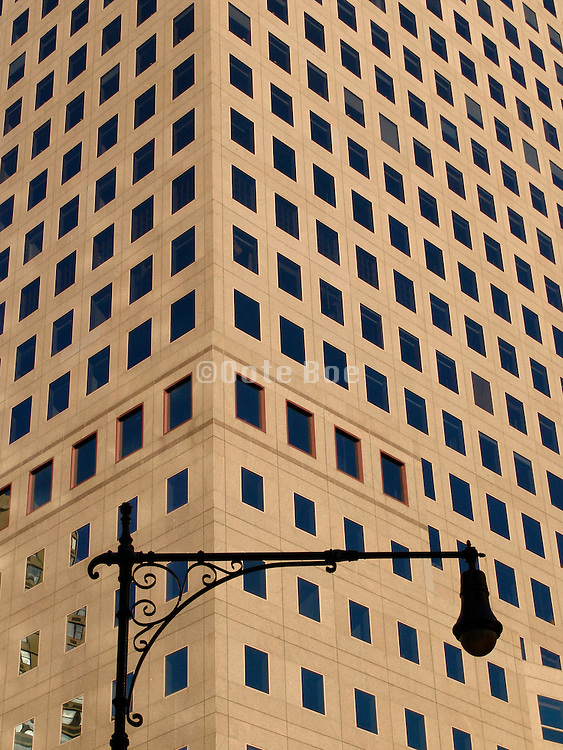 Close up of an office high rise with old lamppost in front of it.