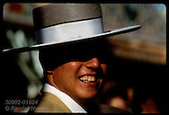 Young man in traditional Cordobes hat flashes smile amid gaiety of Feria de Abril fest; Seville. Spain