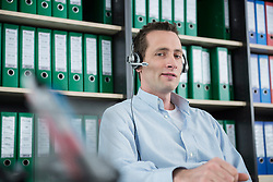 Portrait young man sitting office headset