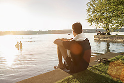 Young man sitting at lakeside during sunset and his friends swimming in lake, Bavaria, Germany