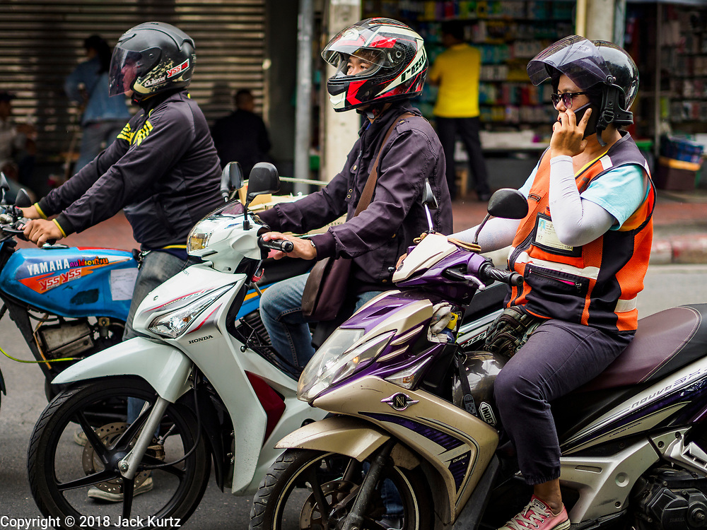 31 JULY 2018 - BANGKOK, THAILAND: Commuters on motorscooters in Chinatown. Bangkok's Chinatown district is one of the largest Chinatowns in the world. It was established in 1781 when Siamese King Rama I gave the Chinese community in Bangkok land outside of Bangkok's city walls so he could build his palace (what is now known as the Grand Palace). Chinatown is now the heart of the Thai-Chinese community. About 14% of Thais have Chinese ancestry.    PHOTO BY JACK KURTZ