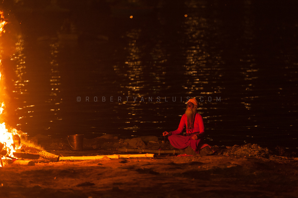 A sadhu meditates at a funeral pyre at the Harischandra cremation ground, Varanasi, India. Photo ©robertvansluis.com