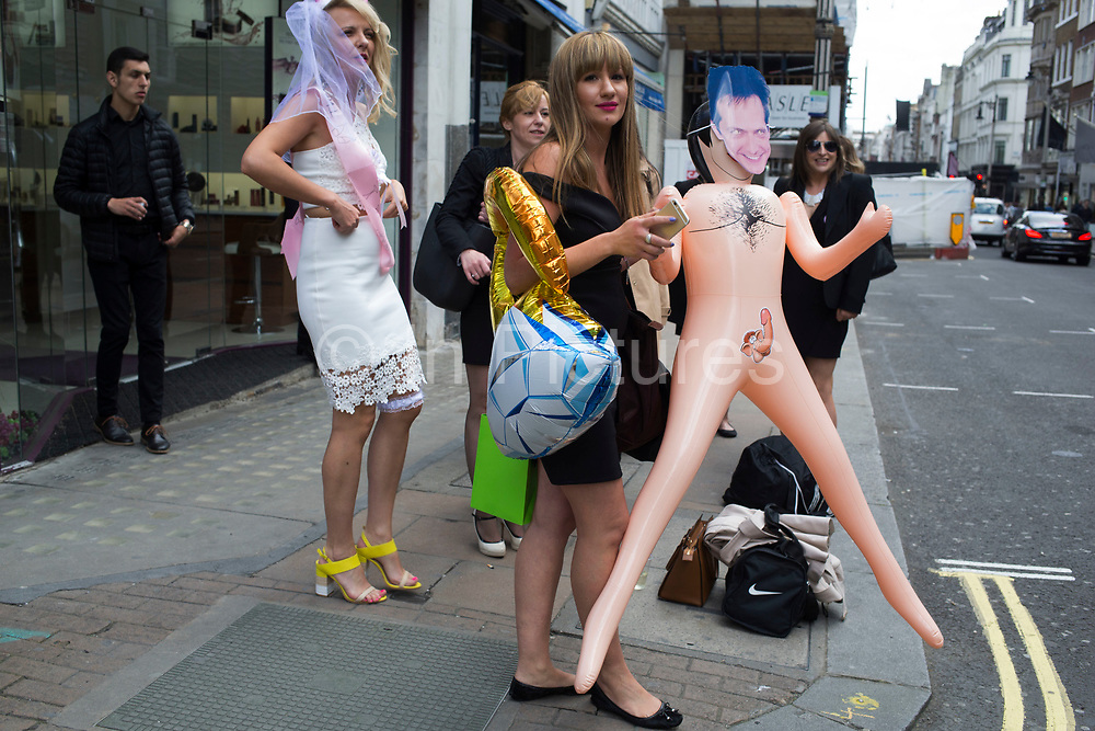 Hen party group with a crude blow up naked man doll gathering on Bond Street in London, United Kingdom. A bachelorette party, hen party, hen night or hen do, is a party held for a woman who is about to get married. The terms hen party, hen do or hen night are common in the UK.
