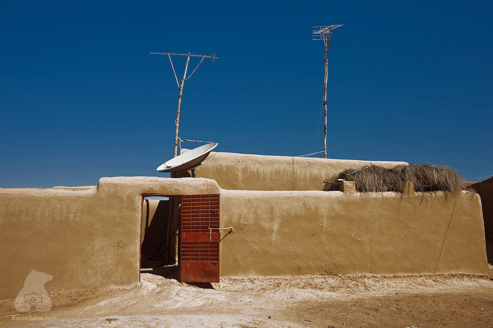 A satellite dish and television antennas are erected on a mud house in Sibé, a small fishing village on the shore of the Niger river, Mali.