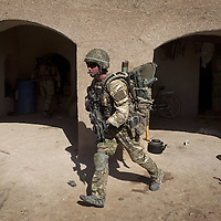 A British soldier of the Pathfinder Platoon, part of 16 Air Assault Bde's elite BRF (Brigade Reconnaissance Force) dashes from one building to another as his team clears a compound whilst on an operation in the village of Kakaran in Helmand Province, Southern Afghanistan on the 14th of March 2011.