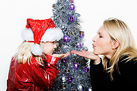 indoors picture of a little girl with her mother preparing christmas tree on isolated white background