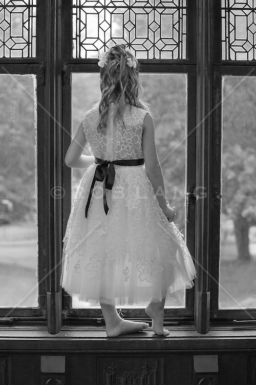 little girl in a formal dress looking out a window in a mansion