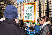 "Protesters outside the British Houses of Parliament holding a placard saying ""Keep Our NHS Public"".  They are demonstrating against the government section 75 privatization regulations which they believe will force the National Health Service into privatization."