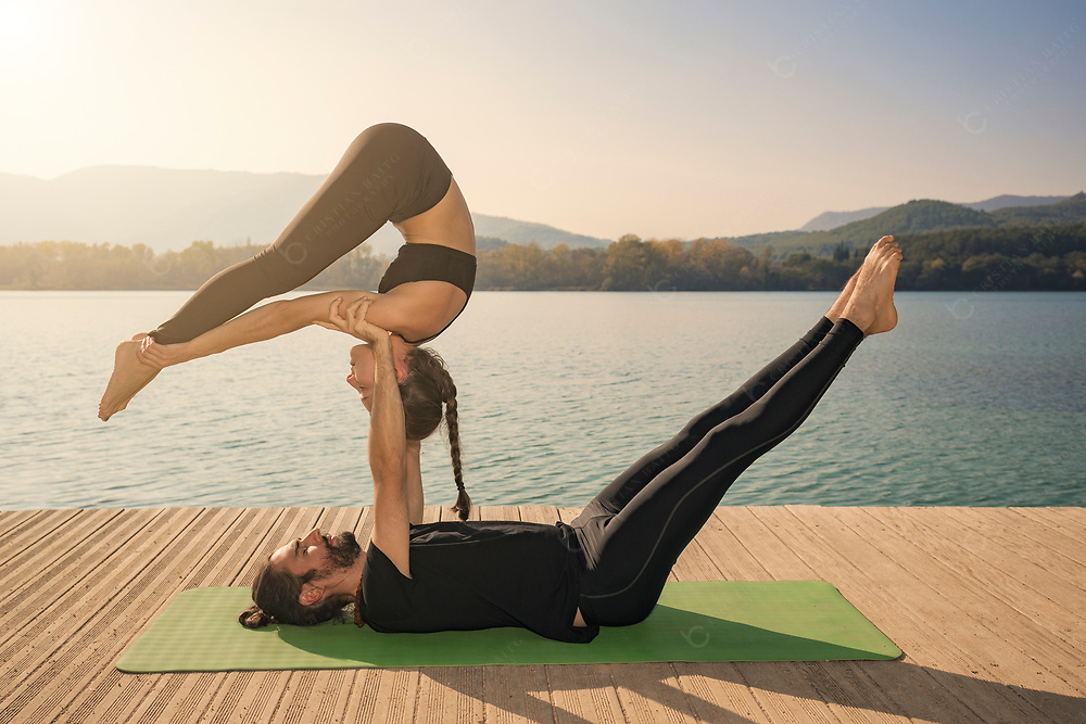 Couple practicing acroyoga in nature at beautiful lake at sunset time Couple practicing acroyoga in nature