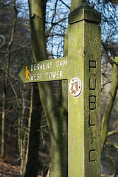 """Public Footpath sign post pointing the way to the west tower of the Derwent Reservoir in Derbyshire, England. <br /> The middle of three reservoirs in the Upper Derwent Valley, the higher reservoir being Howden to the North and the lower being Ladybower to the south. Between them they provide practically all of Derbyshire's water, as well as to a large part of South Yorkshire and as far afield as Nottingham and Leicester.<br /> Begun in 1902 this neo-Gothic solid masonry dam wall is built from huge stones that were transported along a specially created railway from the quarries at Grindleford. Over 1,000 workers lived in a specially constructed and self-contained town of Birchinlee also known as """"Tin Town"""". Derwent reservoir began being filled in November 1914, and overflowed for the first time in January of 1916. Covering an area of 70.8 hectares (175 acres) and at its deepest point is 34.7 metres (114 ft) the dam can support a total of 9.64 million cubic metres of water.<br /> For 6 weeks during the Second World War the reservoir was used by the pilots of the 617 Squadron """"the Dambusters"""" to practice their low-level flying skills needed for Operation Chastise, because of the Derwents similarity to the operations German target. In for 2 weeks in 1954 the the sound of Lancaster bomber engines could be heard again over the Derwent as the reservoir stood in for the German dams a second time. This time for the filming of the """"The Dambusters"""" starring Richard Todd as Guy Gibson. The west tower of the dam wall is home to Derwent Valley Museum and includes a permanent memorial to 617 Squadron to which is visible even when the Museum is closed. <br /> <br /> 22  March 2015 Image © Paul David Drabble www.pauldaviddrabble.co.uk"""