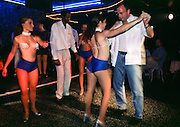 HAVANA, CUBA: Tourists dance with entertainers in the Club Las Vegas, a popular nightspot in Havana, Cuba. The entertainers perform a raucous cabaret show and then dance with the tourists who come to the club. Cubans who go the club pay the cover charge and for their drinks with Cuban pesos. Tourists have to pay with US dollars. Tourism has become a major source of foreign exchange for the Cuban government.    Photo by Jack Kurtz  WOMEN  TOURISM  ECONOMY   CULTURE     LABOUR